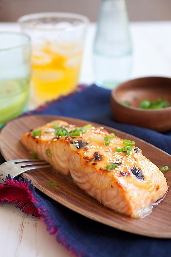 Japanese miso-glazed broiled salmon garnished with chopped scallions in a wooden serving dish.