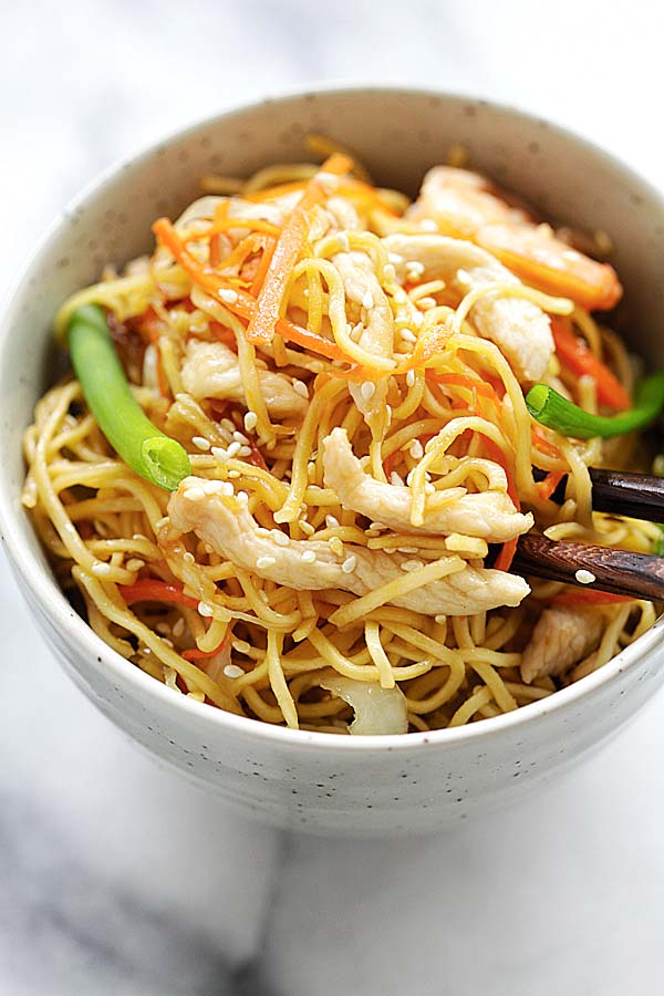 Chow Mein in a Chinese bowl with chicken, shrimp and vegetables, served with a pair of chopsticks.