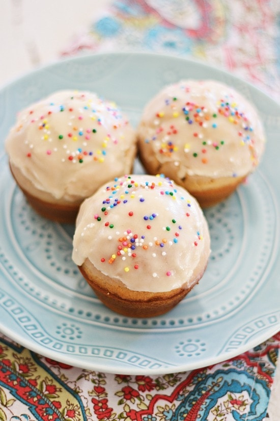 Easy and cute mini glazed doughnut muffins coated with colorful sprinkles.