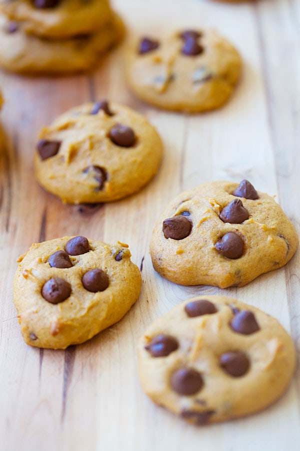 Easy and quick homemade chocolate chip cookies made with pumpkins on wooden chopping board.