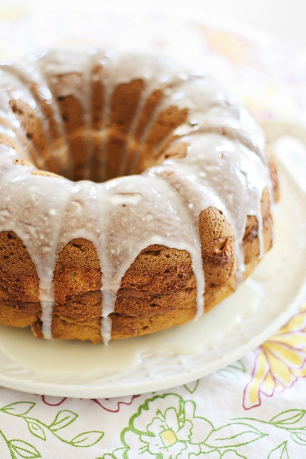 A slice of easy and delicious homemade bundt cake recipe with pumpkin and cream cheese served in a plate with a fork.