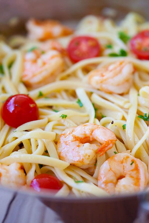 A plateful of shrimp scampi served with linguine pasta and cherry tomatoes.