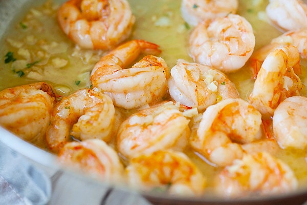 Shrimp in garlicky and buttery shrimp scampi sauce in a skillet.