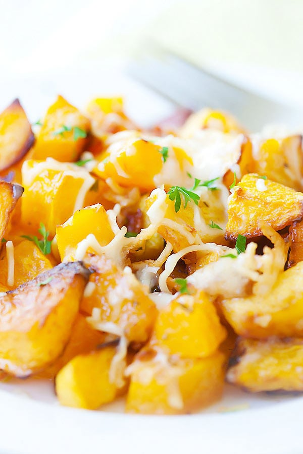 Roasted butternut squash cubes with garlic, parsley, and Parmesan cheese on top.