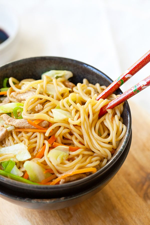 Popular Yakisoba or Japanese fried noodles in a bowl with a pair of red chopsticks.
