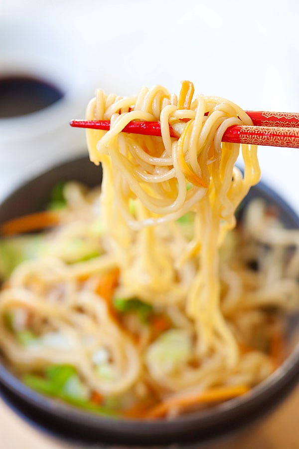 Yakisoba or Japanese fried noodles picked with a pair of chopsticks in a bowl ready to serve.