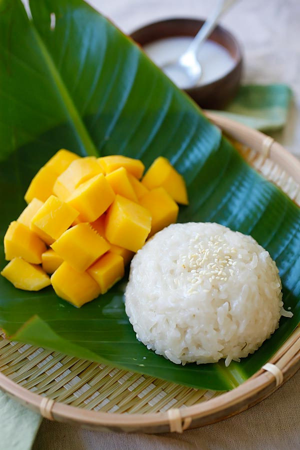 Mango sticky rice with coconut milk and fresh mangoes served on banana leaves.