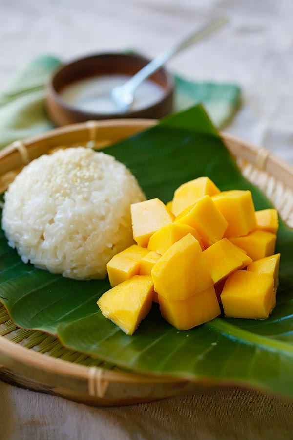 Easy and delicious Thai dessert Mango sticky rice recipe served on a banana leaf.