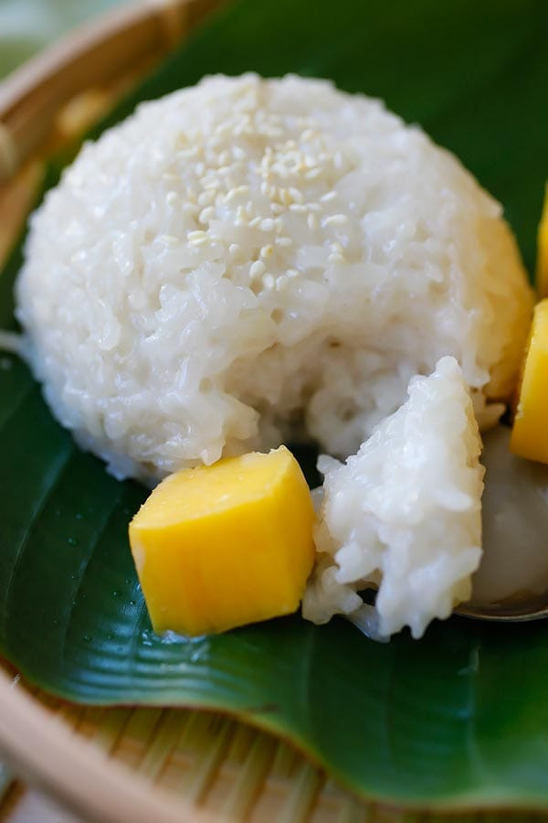 Sweet sticky rice recipe with coconut milk and fresh mangoes with a spoon.