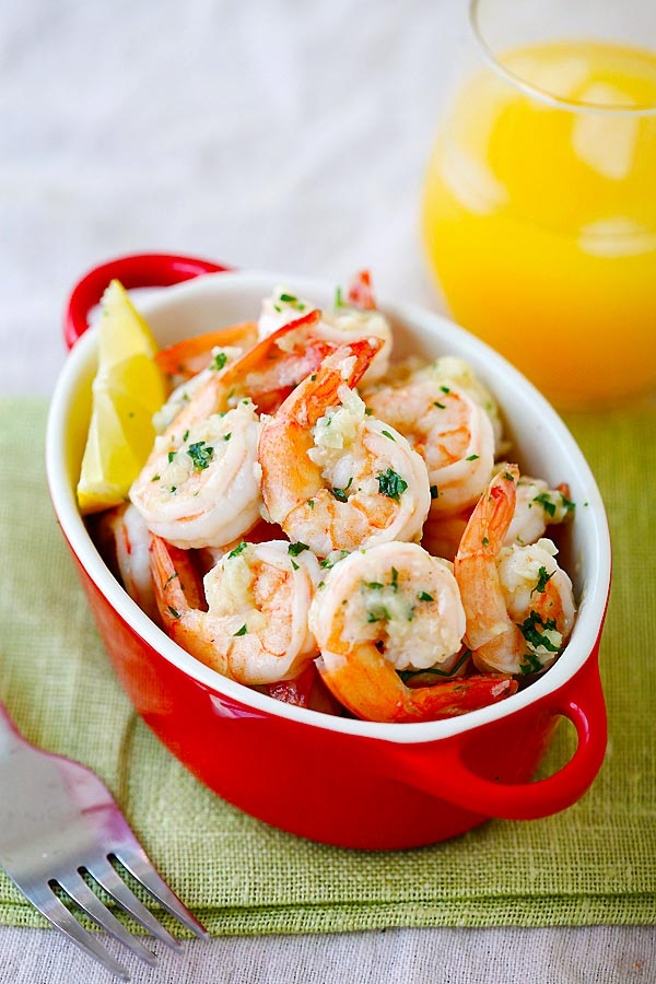 Lemon Garlic Shrimp in a serving dish, topped with parsley and a lemon wedge on the side.