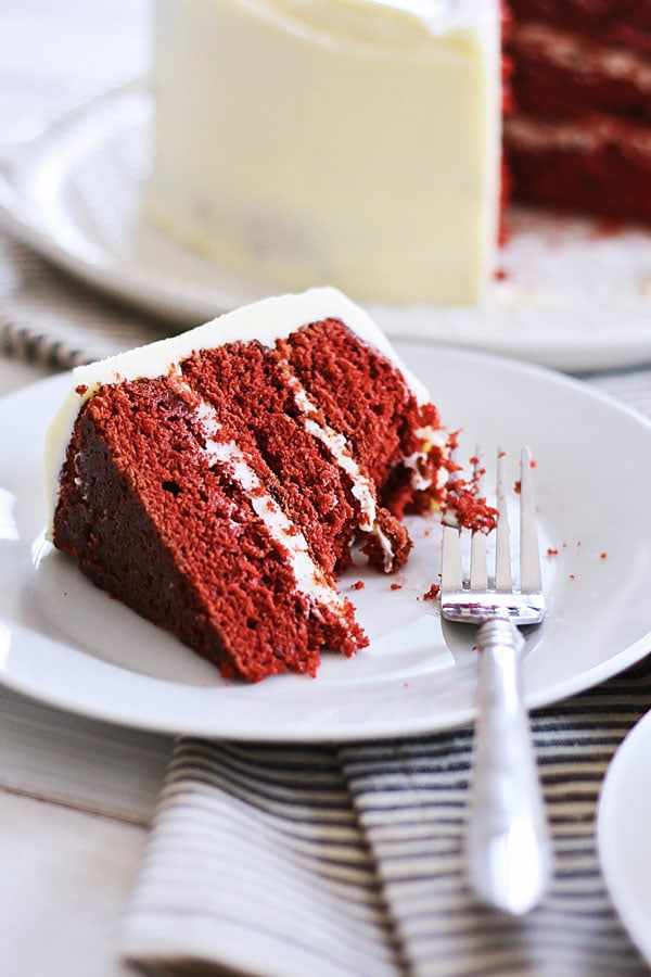 A piece of easy and delicious cake loaded with cream cheese frosting served in a plate with a fork.
