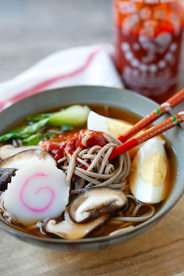 Japanese soba noodles with spicy Sriracha broth in a bowl.