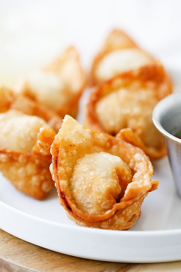 A plate of fried wontons ready to serve with sweet and sour sauce.