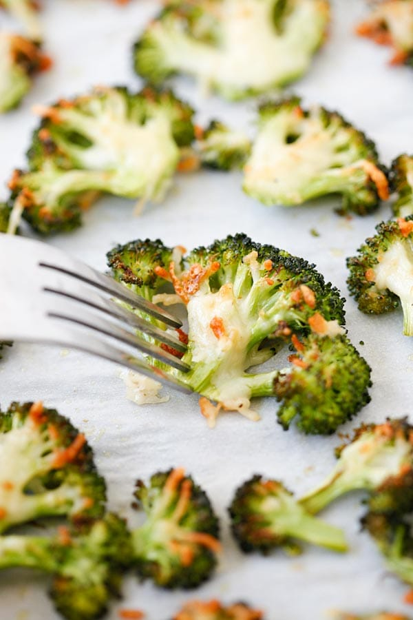 Parmesan Roasted Broccoli poked with a fork, ready to serve.