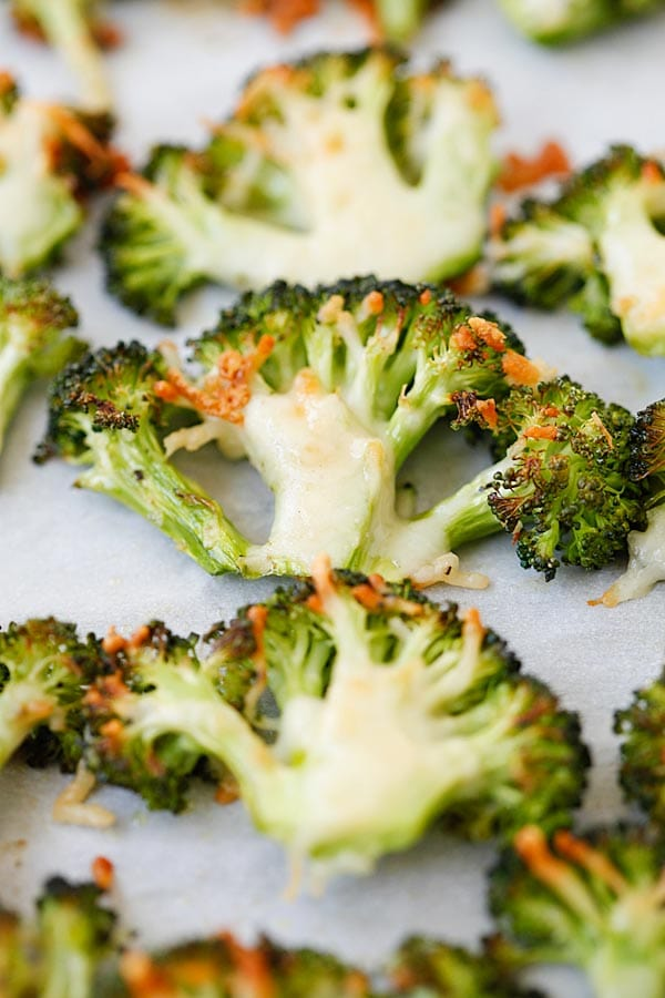 Easy oven roasted broccoli with Parmesan cheese on parchment paper.
