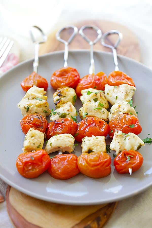 Grilled Greek Chicken Kebab with garlic, lime juice, olive oil and grape tomatoes on a plate.