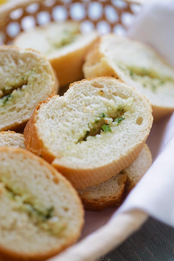 Close up photo - slices of French bread with garlic butter spread on them.
