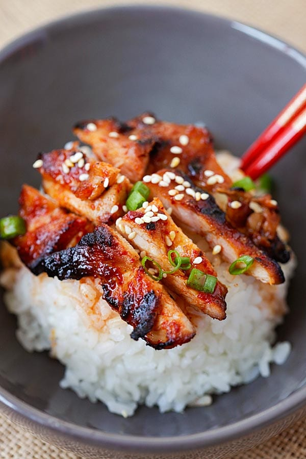 Close up of Korean chicken with spicy gochujang sauce, with sesame seeds.