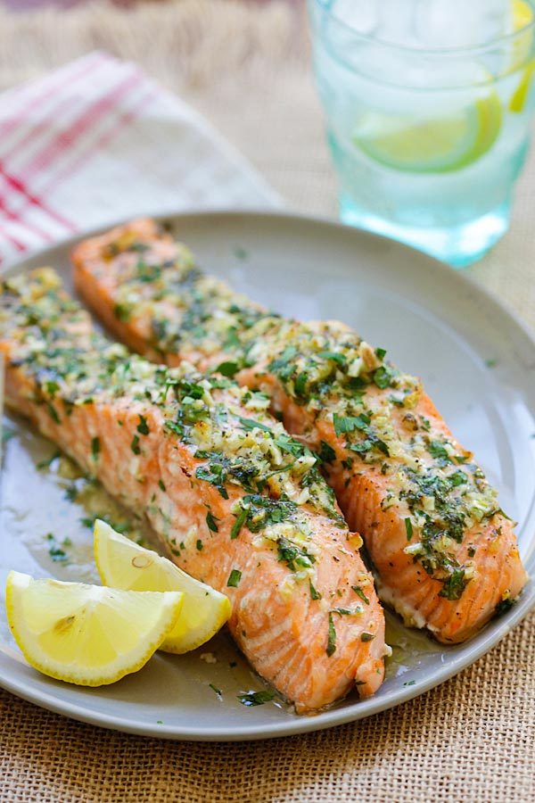 Easy and quick Garlic Herb Roasted Salmon marinade with butter, garlic, herb and lemon in a plate.