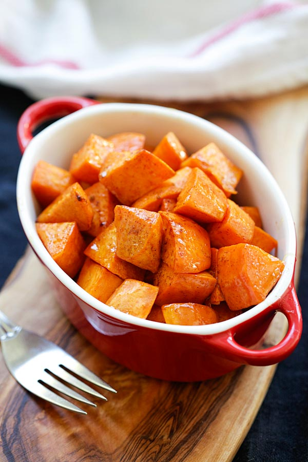 Easy and quick honey Cinnamon Roasted Sweet Potatoes in a red serving dish.