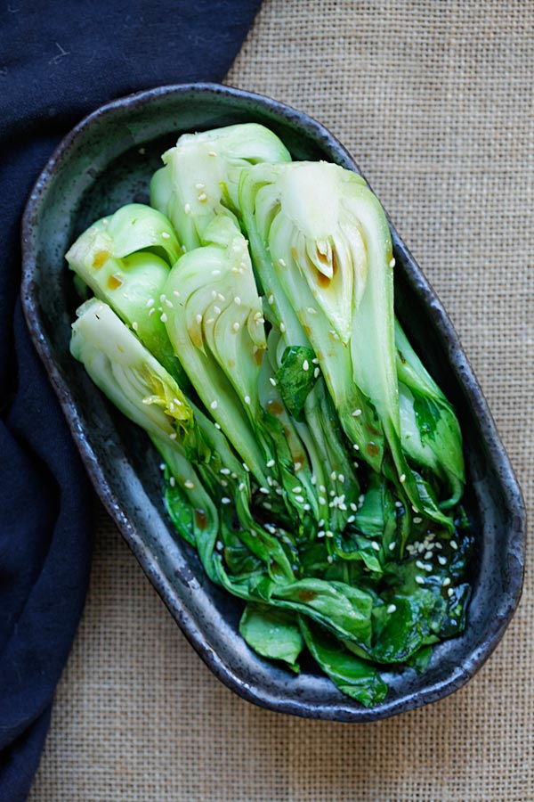 Easy roasted bok choy with light soy sesame dressing in serving dish.