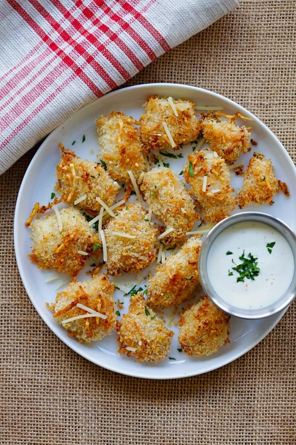 Top down view of homemade easy chicken nuggets recipe with ranch dressing, breadcrumbs and Parmesan cheese in a plate, with a side of dipping sauce.