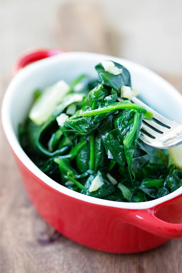 Healthy homemade sauteed baby spinach with garlic butter picked with a fork, ready to serve.