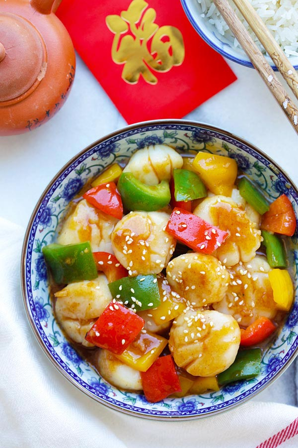 Easy and quick Szechuan scallops stir fry with fiery Szechuan sauce and bell peppers serve in a plate.