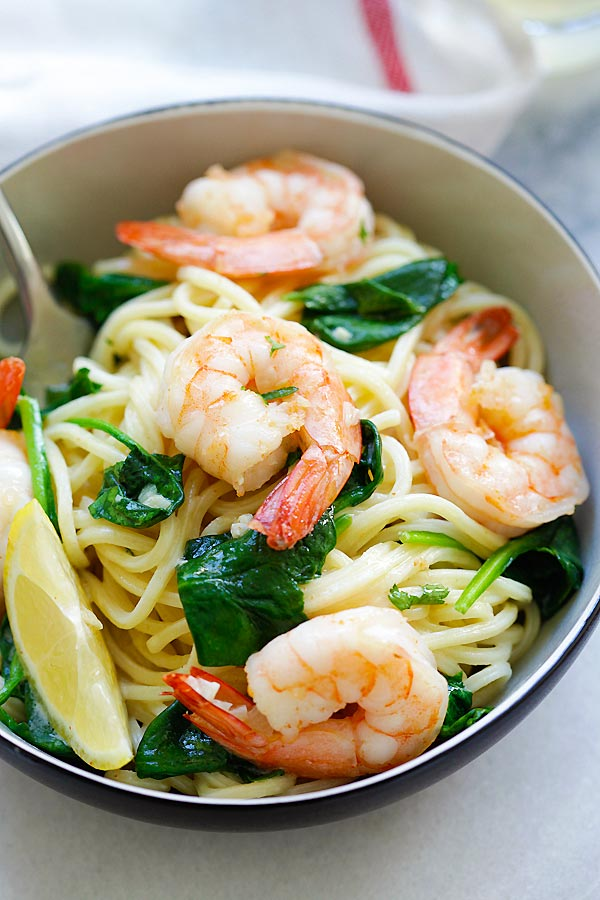 Quick and easy homemade spaghetti with shrimp and spinach in garlic butter sauce serve in a plate.