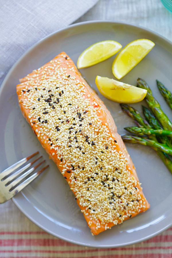 Healthy baked sesame salmon dish in a plate with asparagus and sliced lemon.