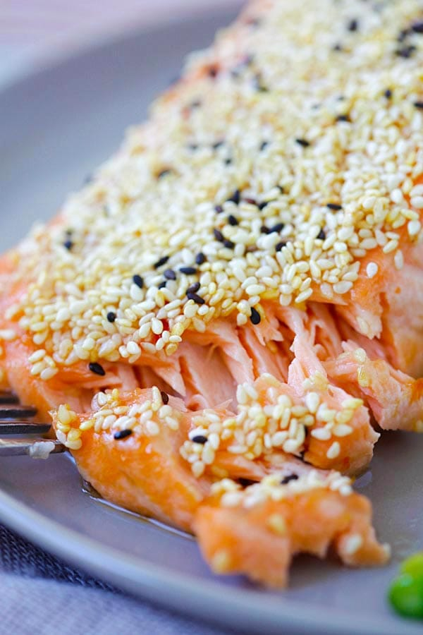 Sesame salmon fillet cut open with a fork, ready to serve.