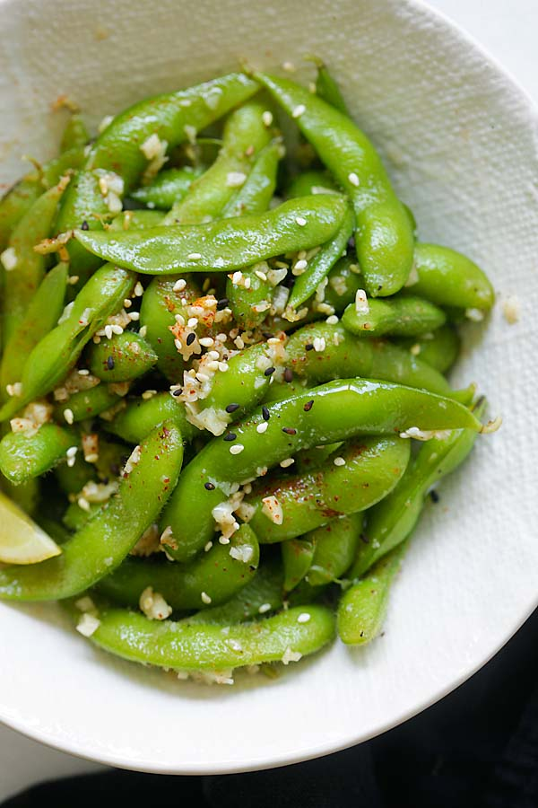 Garlic butter edamame topped with sesame seeds in a bowl.