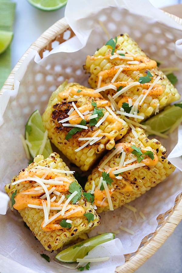 Easy and quick recipe for Mexican street corn with Chipotle seasoning, spicy mayo, Parmesan cheese, lime and cilantro.