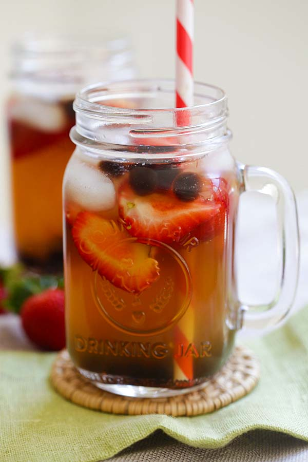 Healthy and refreshing summer iced green tea with strawberry and tapioca pearl boba served in a jar glass.