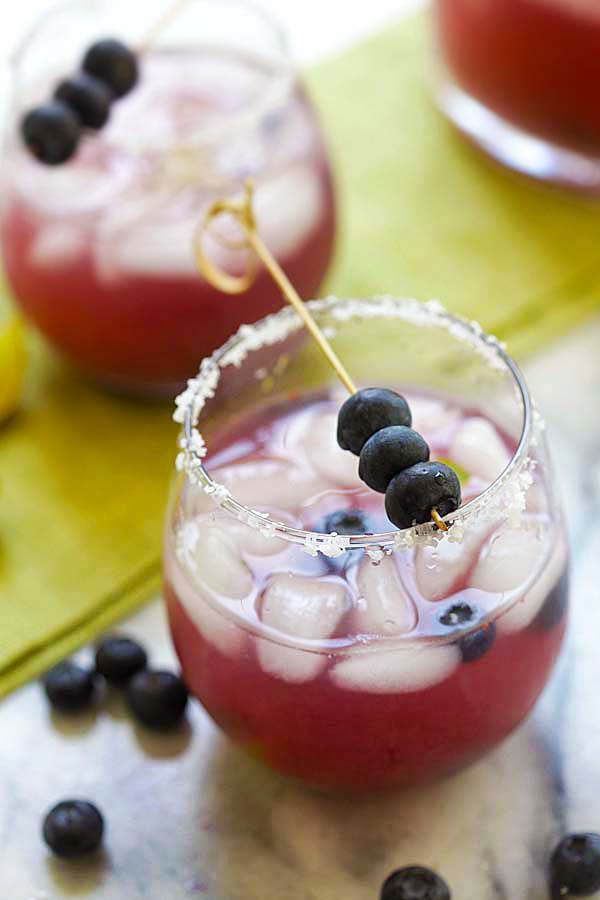 Easiest and booziest blueberry margarita recipe with silver tequila and blueberries served in a cocktail glass.