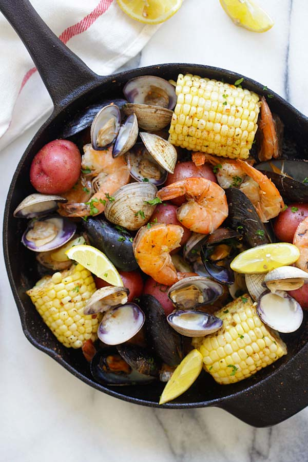 Traditional clambake recipe with seafood in a skillet.