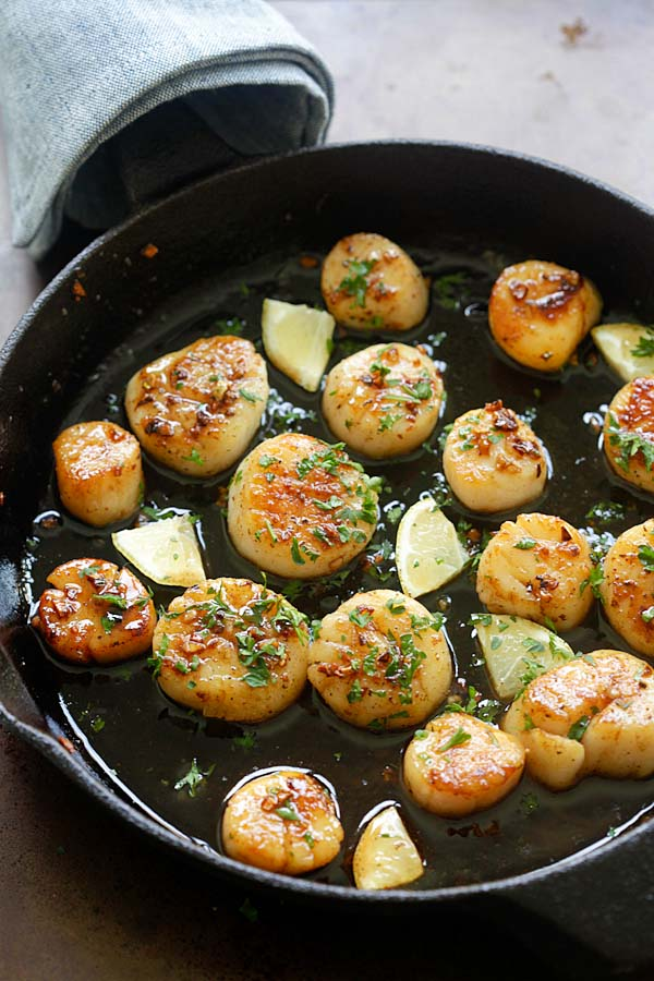 Brown butter honey garlic seared scallops in a skillet.