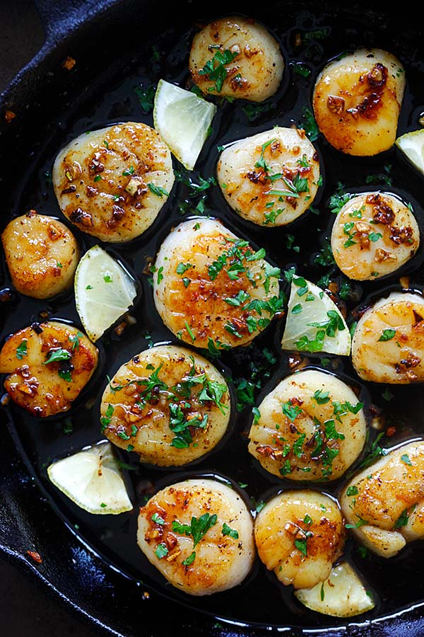 Top down view of brown butter honey garlic scallops with garlic sauce in a skillet ready to serve.
