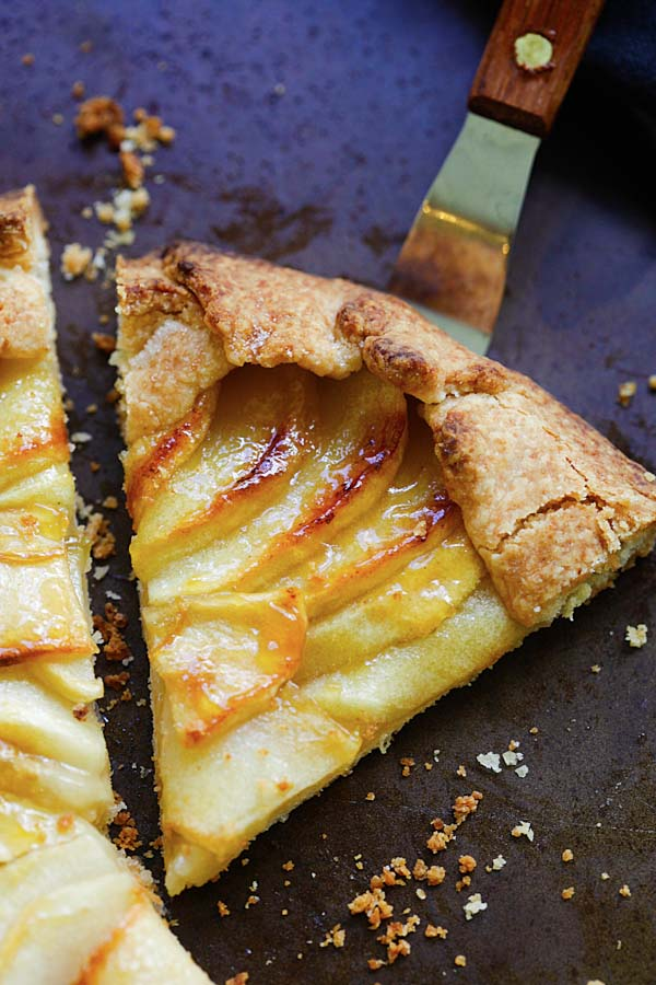 Slice of homemade oven-baked apple tart with scalloped apples in buttery, flaky crust, ready to serve.