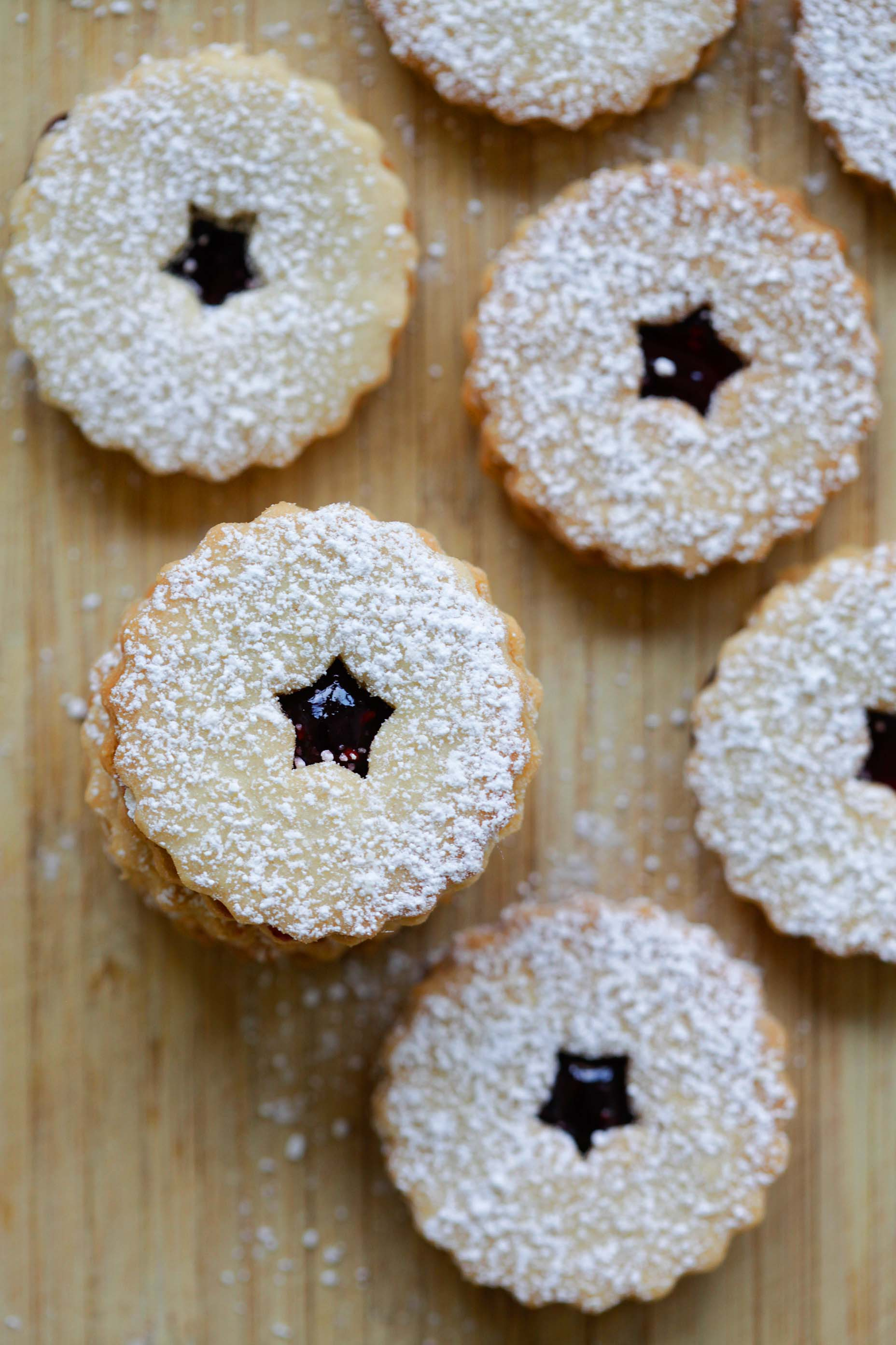 Easy baked mini buttery Linzer tarts with raspberry jam dusted with powdered sugar.