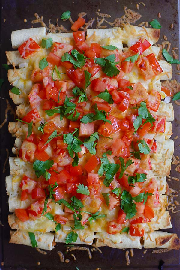 Easy and quick baked Mexican cheesy taquitos topped with chopped tomatoes, diced onions, bell peppers and shredded cheese on a baking tray.