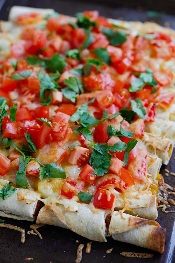 Tasty baked Mexican style rolled tacos with tomatoes, onions, bell peppers and cheese.