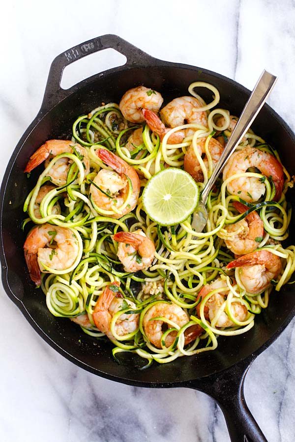 Sauteed brown butter cilantro lime shrimp zucchini noodles in skillet with a fork.