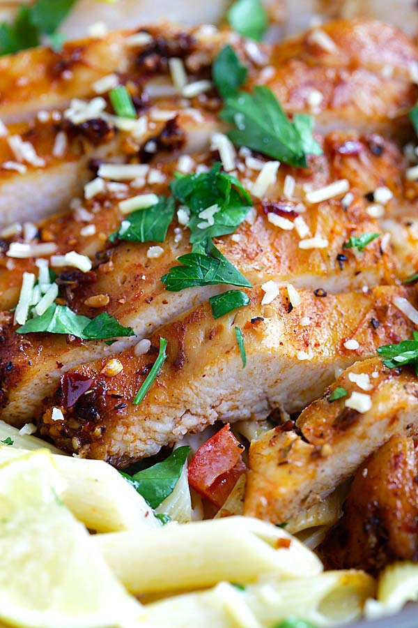 Close up easy blackened chicken with cajun marinade on top of creamy pasta ready to serve.