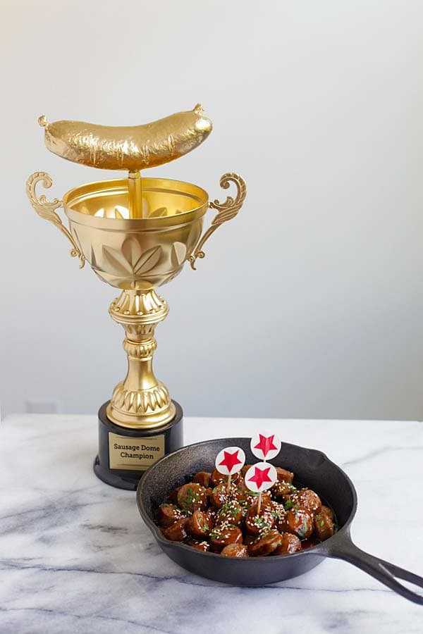 Delicious and easy honey barbecue sausage bites in a skillet, with a trophy.