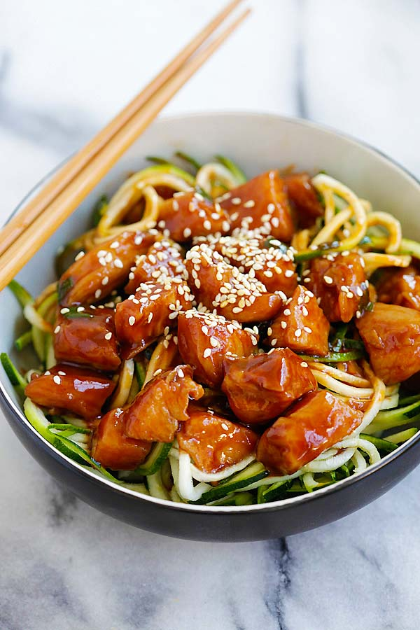 Healthy zucchini zoodles with sweet and spicy honey sriracha chicken on top.
