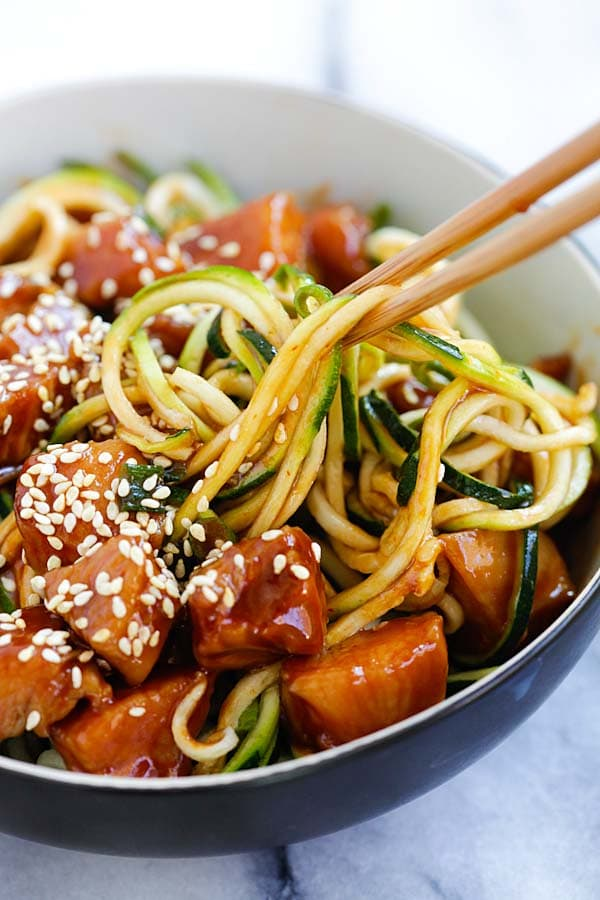 Easy healthy zoodles with sweet and spicy honey sriracha chicken, picked with a pair of chopsticks.