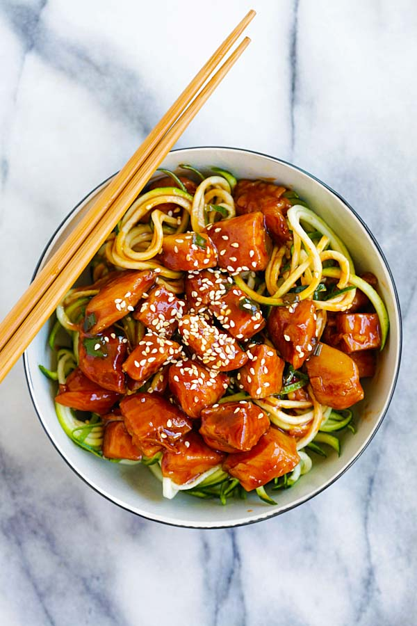 Top down view of easy and quick stir fry honey sriracha chicken on top of zucchini noodles in a bowl.