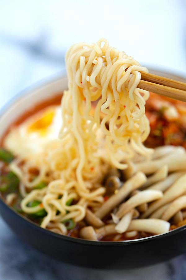 Close up kimchi ramen picked with a pair of chopsticks.