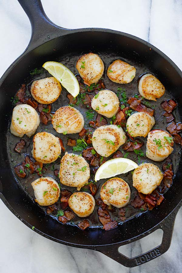 Top down view of seared scallops with crispy bacon bits sauteed in lemon butter sauce, ready to serve.